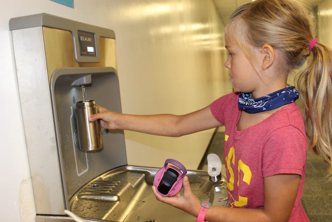 Kate England, a second-grader at Ranch Heights Elementary School, fills up her water bottle for class.