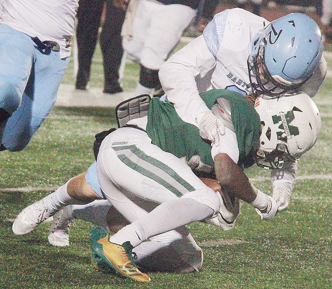 Bartlesville High linebacker Hunter McClintock, left, swallows up a Muskogee player during the 2019 football clash between the teams at the Indian Bowl.