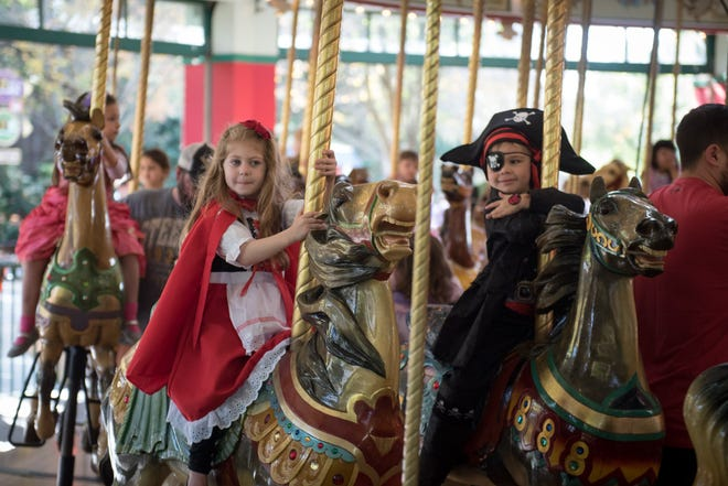 Costumed kids ride the carousel at a previous Boo at the Zoo event. It begins this year next Friday. [Grahm S. Jones]