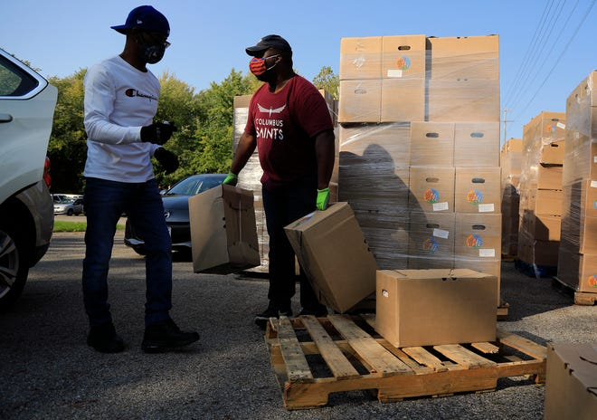 United States Department of Agriculture program Farmers Feeding Families brought a semi truck full of food to United Faith International Church in Columbus, Ohio on October 6, 2020.  Volunteers George Cunningham Sr., left, and Leron Carlton, center, load boxes of food into cars. The church received around 1,000 boxes, with each box having two days worth of food for a family of four.
