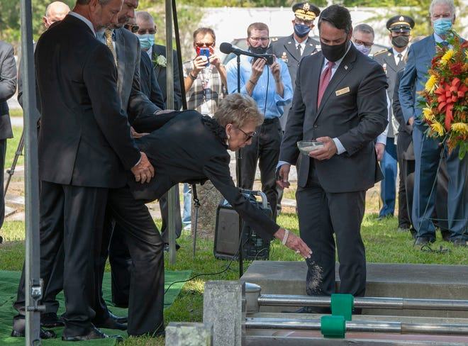 Alice Foster places dirt on the casket of her late husband, former governor Mike Foster, at the graveside service in Franklin on Wednesday.