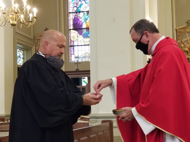 Judge Steven Miller of Thibodaux receives communion from Archbishop Thomas Rodi of Mobile, Ala., during Wednesday's Red Mass at St. Joseph Cathedral in Thibodaux.