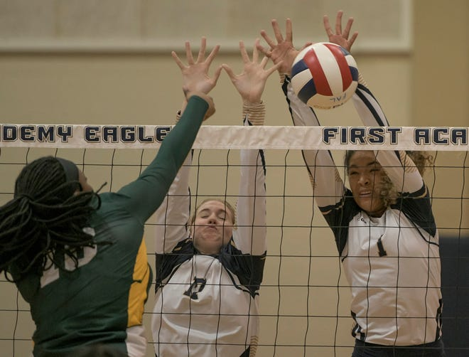 First Academy's Kali Walker (1) and Morgan Henderson (17) go up for a block during Tuesday's match against Ocoee Central Florida Christian Academy at the Family Life Center in Leesburg. [PAUL RYAN / CORRESPONDENT]