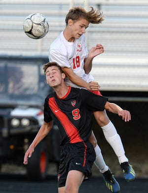 Fairview's Nathan George, left, and Girard's Mason Artz leap for the ball in the District 10 boys soccer game Wednesday at Fairview's Keck Field at Bestwick Stadium.