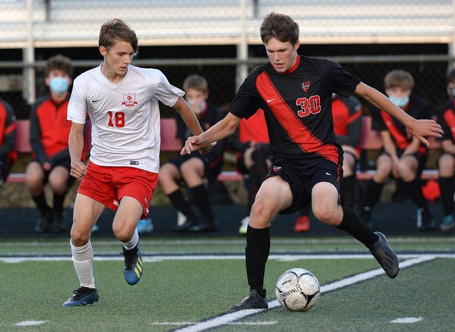 Girard's Mason Artz, left, and Fairview's Justin Noble, right, battle for the ball in the District 10 boys soccer game Wednesday at Fairview's Keck Field at Bestwick Stadium.
