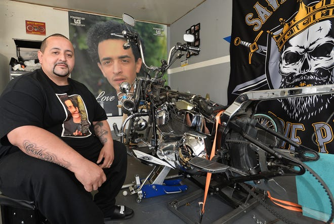 In the garage of his Erie home on Monday, Jose Rosario Sr, 41, is rebuilding a 2002 Harley-Davidson motorcycle, at right, in memory of his son, Jose Rosario Jr (shown on the banner in the background and on Rosario's t-shirt), who was 18 when he was fatally shot on Oct. 15, 2018, at the back door of his apartment on Erie's east side. The homicide is still unsolved.