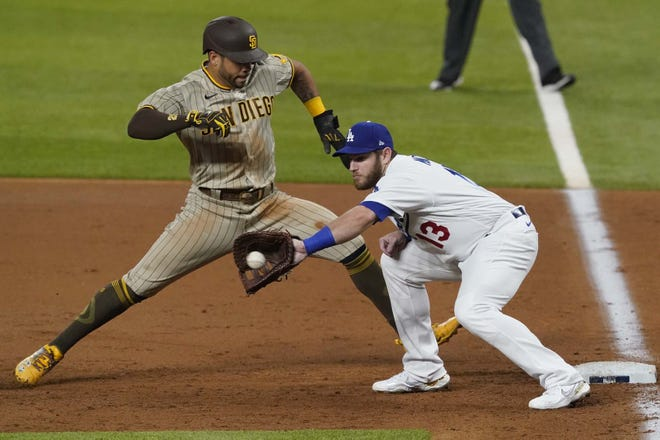 San Diego Padre Tommy Pham (28) runs safely back to first base as Los Angeles Dodgers first baseman Max Muncy catches a pickoff attempt during Game 1 of a National League Division Series Tuesday in Arlington, Texas. [TONY GUTIERREZ / AP]
