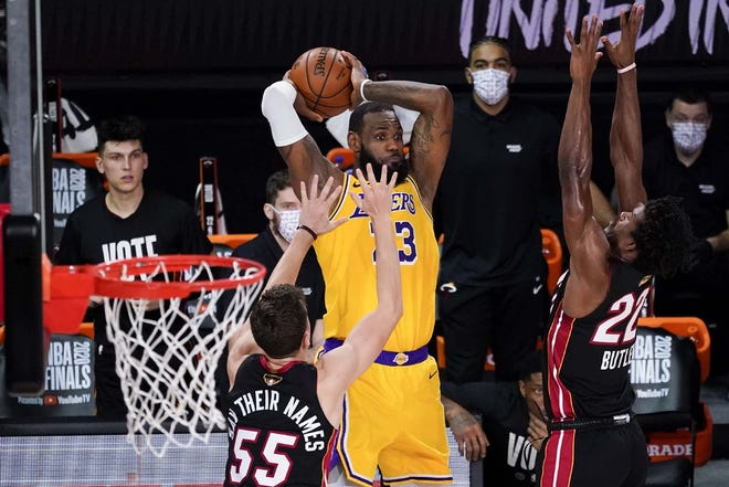 Los Angeles Lakers forward LeBron James passes between Miami Heat guard Duncan Robinson (left) and forward Jimmy Butler during the second half of Game 4 of the NBA Finals Tuesday in Lake Buena Vista, Florida.[JOHN RAOUX / AP]