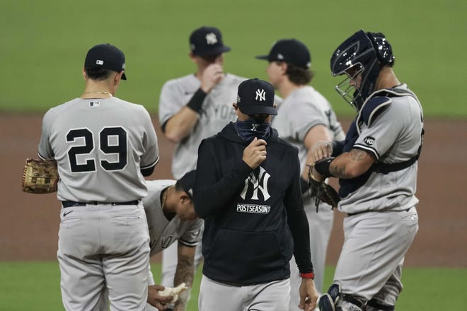 New York Yankees manager Aaron Boone adjusts his mask after he pulled pitcher Adam Ottavino during the fifth inning of Game 2 of an American League Division Series against the Tampa Bay Rays Tuesday in San Diego. [JAE C. HONG / AP]