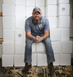 Cugino's Sausage Co. owner Christopher Condon takes a brief break Wednesday amid stacks of Styrofoam boxes used to ship out orders of his company's authentic, old world-style Italian sausage from Cugino's headquarters in a Mandarin office park.