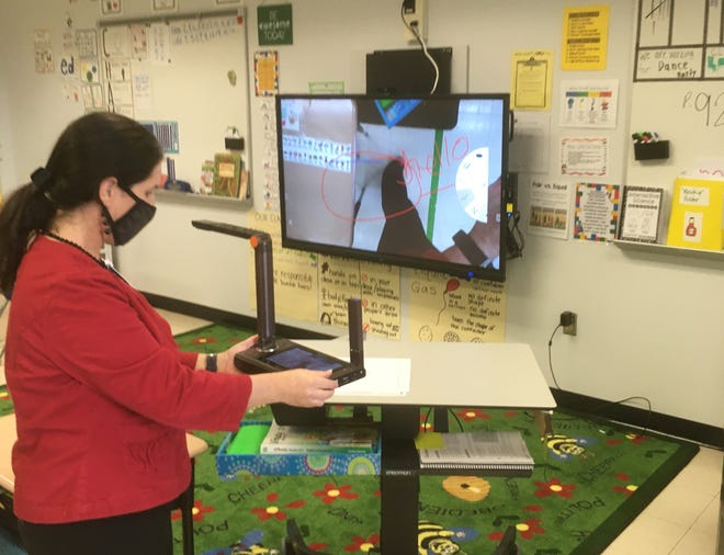 Duval schools' employee  Suzanne Capasso operates a  hand-held document camera  that can record images and wirelessly  project them onto the interactive monitor at the front of a classroom at Northwestern Legends Elementary School.