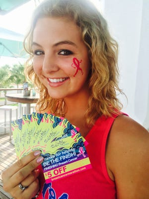 An employee at Salt Life Food Shack holds discount coupons for $5 off, which will be given to diners who add a donation to The Donna Foundation in October.