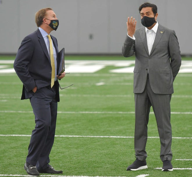 Jaguars owner Shad Khan (right) and Mayor Lenny Curry talk before the start of Monday's presentation on the latest plans for the Lot J development outside TIAA Bank Field.