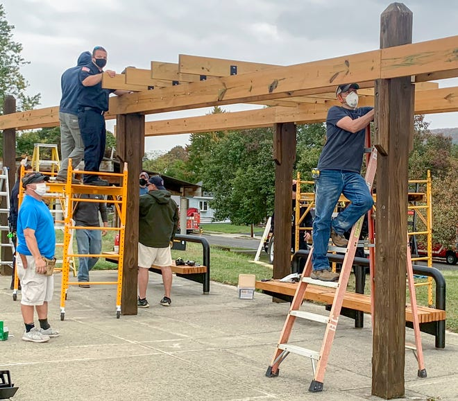 Firefighters from IAFF Local 932 work Wednesday to restore the pavilion adjacent to Corning's Hillvue Park.