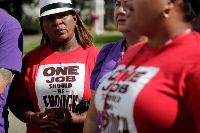 "A woman wears a T-shirt reading ""One Job Should Be Enough"" during a rally calling for an increase in the minimum wage in October 2019 in Miami."