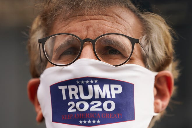 A member of the Jewish Orthodox community wears a mask supporting President Donald Trump as he speaks with journalists on Wednesday in the Borough Park neighborhood of Brooklyn in New York.