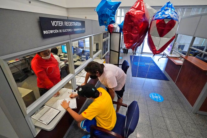 Lucas Saez, foreground, 22, fills out his voter registration form as his father Ramiro Saez, center rear, looks on, Tuesday, Oct. 6, 2020, at the Miami-Dade County Elections Department in Doral. Florida Gov. Ron DeSantis extended the state's voter registration deadline after heavy traffic crashed the state's online system and potentially prevented thousands of enrolling to cast ballots in next month's presidential election. Saez attempted to register to vote six times the night before without any luck.
