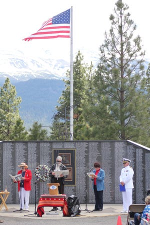 People gather twice a year at the Living Memorial Sculpture Garden off of Highway 97: on Memorial Day and Veteran's Day to dedicate the names of honorably discharged veterans on the Hot LZ Wall. This photo was taken on Memorial Day, 2013.
