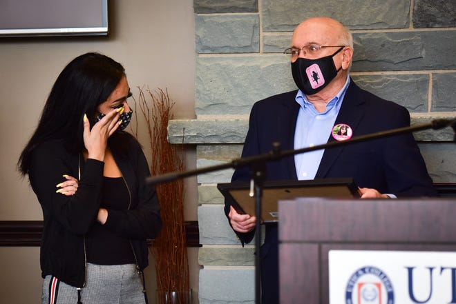 From left, Tiana Guzman wipes away a tear as she is presented with the first award from the Bianca Michelle Devins Memorial Scholarship Fund by Devins' grandfather Frank Williams on Wednesday, Oct. 7, 2020, at Utica College.