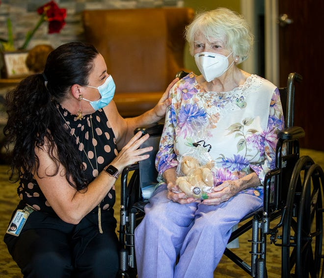 "Monica Quinlan, human resources director for Bridgewater Park Health and Rehab, visits with Theresa Mondo, a resident, after Mondo received her stuffed bear Wednesday afternoon. ""It's something nice and soft to hold onto,"" Mondo said."