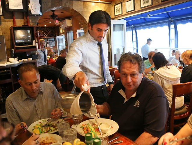 Gabriel Benitez, as server at Caffe Luna Rosa in Delray Beach, fills the water glasses of a table of diners Thursday, March 6, 2014. [Damon Higgins / The Palm Beach Post]