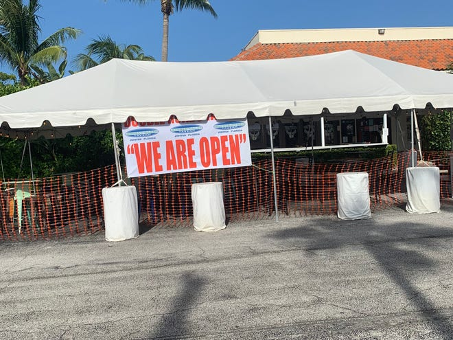 A tent is set up outside Double Roads Tavern in Jupiter for outdoor seating.