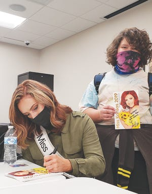 Miss Kansas 2019 Annika Wooton autographs an official Miss Kansas photos for Makyla Brown (right), and other Liberty Middle School students she met with Thursday, October 1 at the Pratt Public Library.