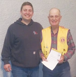 Pratt Lions Club President Andy Lee congratulates Pratt Lions Club member and Past President Denis Rasmussen (right) for his award from Lions International  for 45 years of service and club membership.