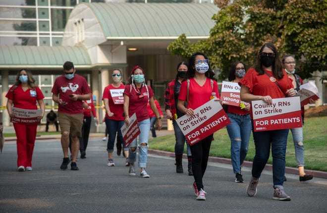 Striking registered nurses walk the picket line on the driveway in front of San Joaquin General Hospital in French Camp on Oct. 7. San Joaquin County has come to a temporary agreement with nurses at the hospital to avoid a possible strike scheduled for Saturday.