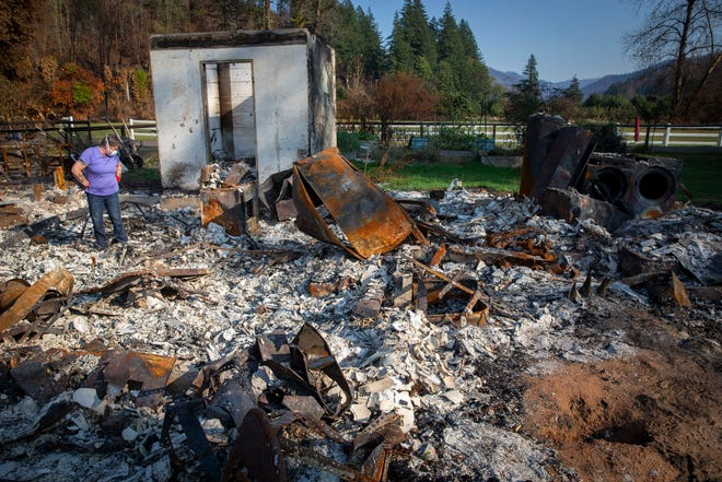 Upper McKenzie Fire Chief Christiana Rainbow Plews searches through the burned remains of her Vida home. FEMA and Oregon are encouraging residents with burned property to first try to get assistance from the government before cleaning up.