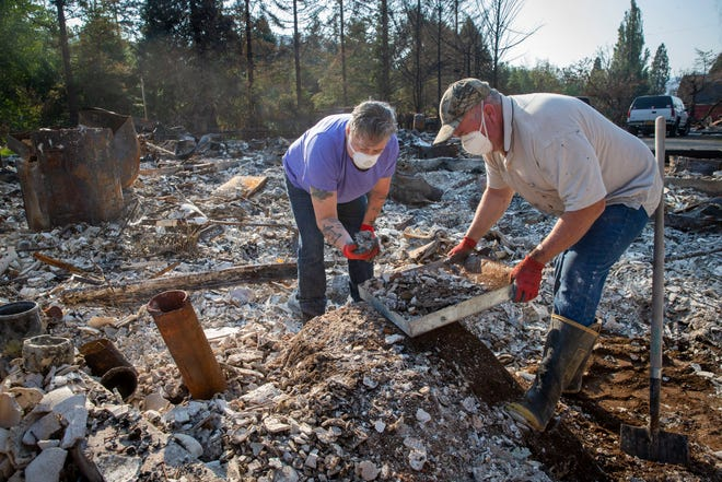 Upper McKenzie Fire Chief Christiana Rainbow Plews, left, works with Clayton Canfield as they sift through the debris of her home this week in Vida. Plews was among the several hundred residents who lost their homes in the Holiday Farm Fire.