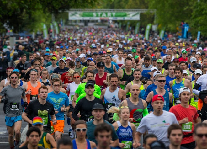 A sea of runners maker their way down Agate Street at the start of the 2018 Eugene Marathon.