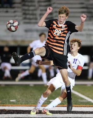 Jason Weber (22) of Green makes a play on the ball while being defended by Evan Wilson (11) of Jackson during Tuesday's  game at Green. Wilson had two goals and two assists to help lead the Polar Bears past the Bulldogs 6-0.