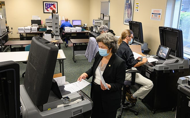 St. Johns County Supervisor of Elections Vicky Oakes members of her staff and the county election canvassing board feed sample ballots into machines during the public pre-election test of the automatic ballot tabulating equipment at headquarters in St. Augustine on Wednesday. The testing, which was open to the public, is to confirm the accuracy of ballot counting machines before the general election on Nov. 3.