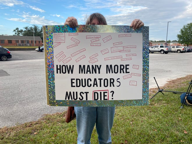 Protester holds up a sign outside Tuesday's New Hanover County School Board meeting