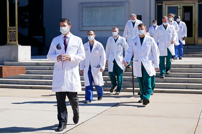Dr. Sean Conley, physician to President Donald Trump, is followed by a team of doctors for a briefing with reporters at Walter Reed National Military Medical Center in Bethesda, Md., on Oct. 3. Trump was admitted to the hospital after contracting the coronavirus.