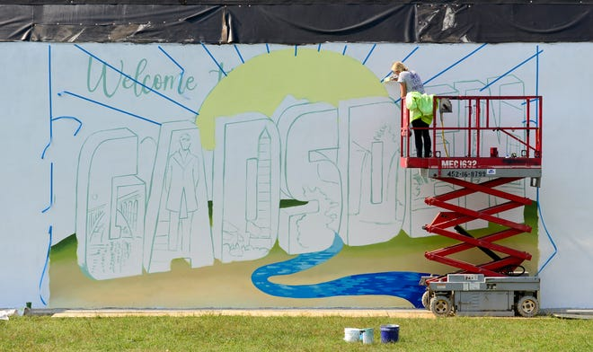 Artist Ali Hval works on a new mural in the 100 block of Broad Street in downtown Gadsden on Wednesday.