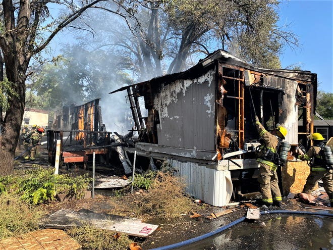 Firefighters work to extinguish a fire that gutted an abandoned East Side mobile home Tuesday.