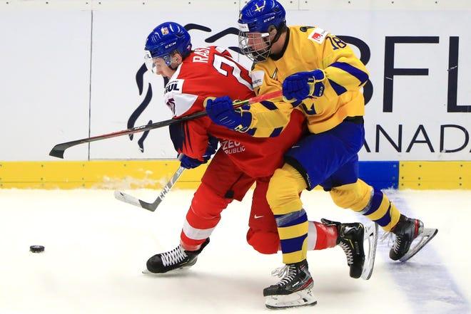 The Czech Republic's Adam Raska (L) and Sweden's Lucas Raymond in their 2020 IIHF World Junior Ice Hockey Championship quarter-final match at Ostravar Arena.