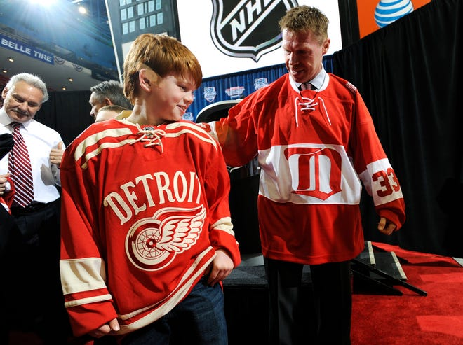 Four-time Stanley Cup champion Kris Draper, right, and his son Kienan, 11, model the jerseys for the 2013 Winter Classic and the alumni game in Detroit.