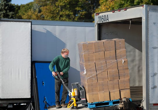 Bill Jacob unloads cases of food from a semi truck for Feeding America's food distribution on Wednesday, Oct. 7, 2020, at Northeast Wisconsin Technical College in Green Bay, Wis. The nonprofit organization has been feeding 500-700 households each time they have food drop-offs in Green Bay.