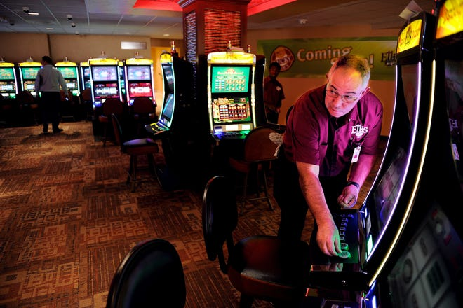 Steve Renfrow, right, a housekeeper with Ellis Park, pulls protective stickers off the buttons on some of the 172 new instant racing machines installed in a renovated section of Ellis Park Thursday afternoon, August 30, 2012.