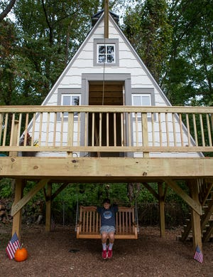 Lincoln White sits under his new two-and-a-half-story A-frame treehouse newly built in his backyard. The treehouse was built for White by Make-a-Wish. White, who was diagnosed with leukemia at age 3, wanted his wish to be permanent so he chose the treehouse instead of a vacation.