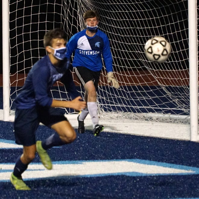 Stevenson goalie Brenden Ware, center, watches the ball roll near his net in the first half of the game.