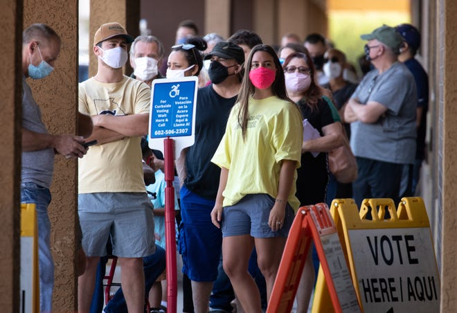 Voters wait in line on Oct. 7, 2020, at the Dobson Palm Plaza Vote Center in Mesa.
