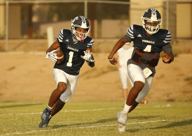 Pinnacle quarterback Devon Dampier (4) blocks for wide receiver Dorian Singer (1) on a designed option play during a practice at Pinnacle High School in Phoenix, Ariz. on Oct. 5, 2020.