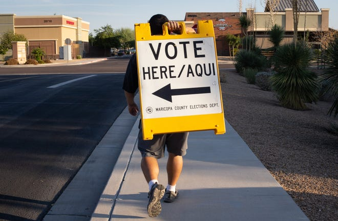 Al Solorzano (poll worker) puts out voting signs at Communiversity at Queen Creek Vote Center on Oct. 7, 2020, in Queen Creek.