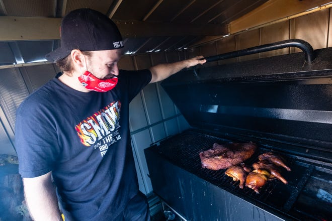 Nick Hartig, owner of Smoke On The Water BBQ & Catering, looks at a brisket and chicken on the smoker behind the restaurant Wednesday, Oct. 7, 2020, in Port Huron. Hartig recently opened the rock'n' roll themed restaurant, which specializes in smoked meats, handcrafted burgers and more.