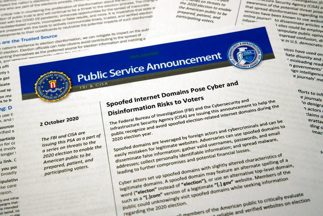 A public service announcement from the FBI and the Department of Homeland Security cybersecurity agency is photographed Tuesday, Oct. 6, 2020. The government agencies have issued a series of advisories in recent weeks aimed at warning voters about problems that could surface in the election — as well as steps Americans can take to counter the foreign interference threat.  (AP Photo/Jon Elswick)