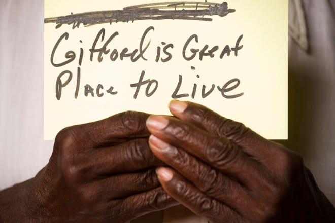 """Victor Hart de Gifford tient une carte indiquant que """"Gifford est un endroit idéal pour vivre"""" lors d'une séance photo en avril 2013 demandant aux résidents d'écrire ce que Gifford signifie pour eux au centre d'activités jeunesse de Gifford."""